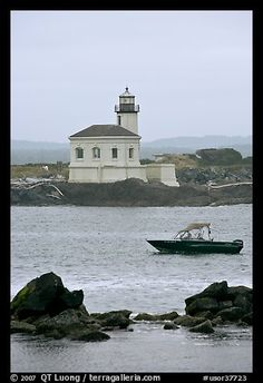 Small boat and Coquille River lighthouse. Bandon, Oregon, USA