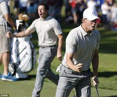 Thomas Pieters and Rory McIloy celebrate after the Belgian sunk his putt on the 13th green...