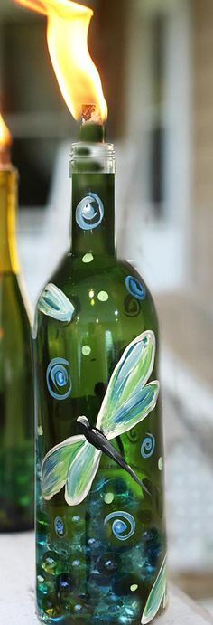 This green wine bottle is hand-painted with glass paint and comes complete with tiki torch wick and ceramic top. Simply fill with citronella and pebbles.