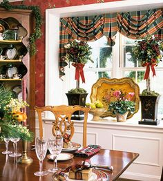 A seasonal display in the dining room window puts a pretty platter on its side instead of on the table. Small wreaths hung in the window frames add to the Christmas spirit./