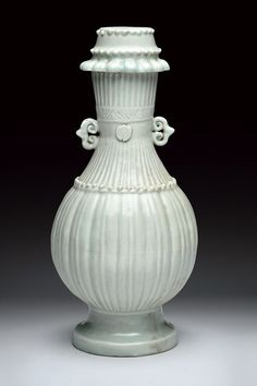 Yingqing vase. Song dynasty, 13th Century.  Slender, elegant shape, with two small handles depicting spirals, at the neck and the shoulder are three rows of spherical pearls. Relieved motifs at the neck and the body. Light porcelain covered by the typical, translucent, pale light-blue glaze. Estimatz 2000.00 | 2500.00 €
