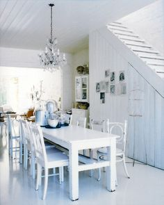 Dining room with mismatched chairs and an open staircase.