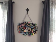 Travel magnet display!! Bought all supplies at Hobby Lobby: -metal chalkboard -ribbon -fleur-de-lis hook Used my Makita to drill 2 holes in the metal board, threaded the ribbon through and knotted in the back to hold. Then I hung it from the hook and attached magnets that I collect from all over the world when I travel. It's heavy, so I made sure to screw into a stud to anchor the hook. Looks like I need a bigger chalkboard!