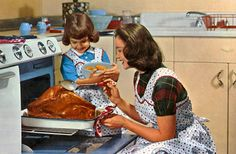 Vintage mom & daughter roasting turkey.