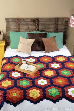 This cozy crocheted afghan gets its style from touchable texture (thanks to a puffy motif design) and a rich retro color palette.