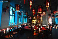 Eine massive Eisenpforte, dahinter dunkles Holz und rote Lampions: asiatisches Essen in besonderer Atmosphäre.