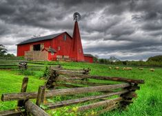 I love all the contrasts here.... The dark blue, stormy looking sky, the green, green grass, the old unpainted fence and the red barn. Awesome picture!