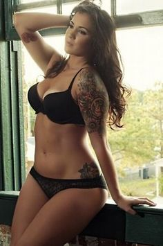Brunette woman in front of a window, in black bra. Arm and hip tattoos