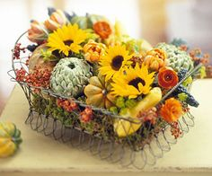 Harvest Basket Centerpiece. Simply fill a wire basket with a layer of moss and a variety of sunflowers, mums, gourds and bittersweet!