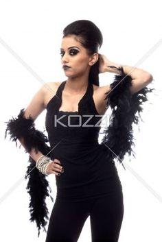 portrait of a beautiful young woman with a feather boa posing. - Portrait of a beautiful young woman with a feather boa posing over white background, Model: Kiran Bahugun