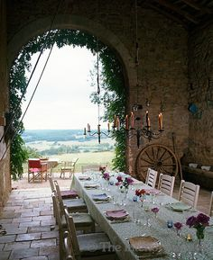 "Designer Kathryn Ireland's Dutch barn in France.  A new style of Al fresco dining (eating outside , from the Italian ""al fresco"" meaning ""outside, at a fresh temperature"").  Plenty of fresh air from the huge arched doorway in this castle style dining area on a stone floor - but with a barn roof to keep you cool on hot summer days and dry in rain."