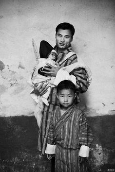 An image which depicts the traditional Bhutanese mens dress, the gho, which is worn by all ages. This particular image also shows the high values held in Bhutan in regards to a mans role in child rearing and as a father. This raises the subject of masculinity and a contrast between Bhutan's and the 'western worlds' perceptions of this // source unknow
