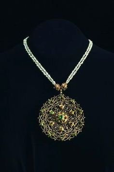 Pendant from the tazra necklace  Fez, Morocco  Late 19th century  Gold, cast and pierced; emeralds and rubies || The tazra necklace included three such pendants decorated with openwork suggesting Hispano-Moorish lattice work, showing that the reputation of the Jewish goldsmiths of Fez and Meknes for delicate workmanship was well-deserved.