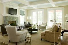 Beautiful coffered ceilings with subtle pop of color and stone facade on fireplace...