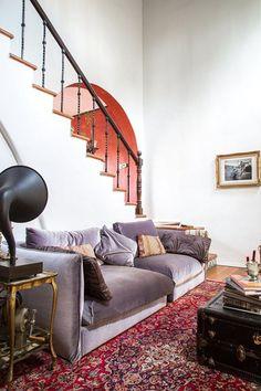 lavender velvet sofa and jewel toned rug and wall paint. #lavender #purple #jeweltones #jeweltoned #wallpaint #redwall #redpaint #rug #vintagerug #persianrug #victrola #chest #vintagechest #purplesofa #lavendersofa #velvetsofa #velvetcouch #couch #sofa