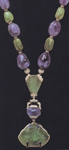 An Art Deco necklace, by Cartier Paris, commissioned in 1927 by the Aga Khan - alternate sapphire and emerald beads and diamond roundels, centring a carved emerald weighing 24.62 carats set above a cabochon sapphire weighing 25.60 carats, the carved emerald weighing 70.46 carats. Image source: Cartier, by Hans Nadelhoffer.