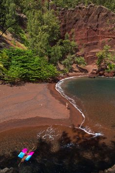 Kaihalulu Bay: In this Sept. 24, 2014 photo, people enjoy the red sand beach at Kaihalulu Bay in Hana, Hawaii. Towering red cinder cliffs surround the bay, and the blue ocean swirls along the red sandy shore. A large lava rock reef juts out in the bay slightly protecting the beach from harsh waves, but swimming is not advised.