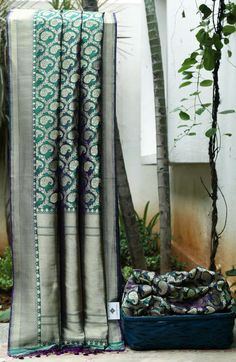 Purple and green shot coloured benares silk . The sari is embellished with gold paisley motifs all over the body
