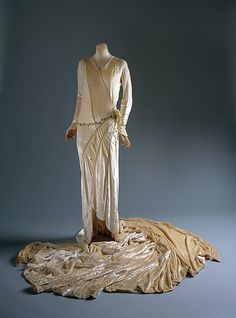 Wedding Dress by Madeleine Vionnet | This 1929 wedding dress is sectioned into shapes throughout its body and train of more than seven feet.  There was an original lace veil, but here the dress without veil is a triumph of linear divisions made by the metallic cord