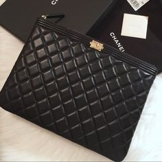 """Auth Chanel Le Boy Black Lambskin Medium O Case 100% Auth Chanel Le Boy Black Lambskin Medium O Case with aged gold hardware. Super popular & hard to find. Sold out in stores! Can be used as a clutch, pouch case or cosmetic bag. Bought in Sept used only ONCE. In pristine flawless condition.  Beautiful inside & out. Interior textile lining is spotless. Comes with original box, dust bag, tag, card card and authenticity card.  Made in Italy. Measures at approx. 10.75""""L x 8""""H x 0.75""""W.  Add'l…"""