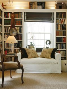 Library/study with white, slipped loveseat, chocolate roman shades with bookcases flanking the window.