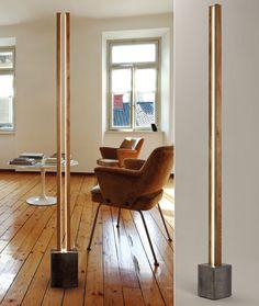 modernes wohnzimmer mit holzfußboden, designer Armsesseln braun, rundem Couchtisch weiß und moderner Stehlampe aus holz