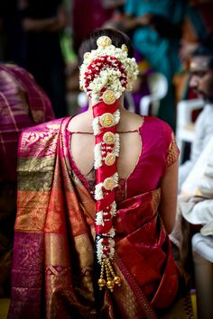 South Indian bride's wedding braid bedecked in flowers and wrapped in ribbons