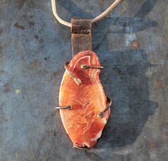 Raw Carnelian slab pendant set in copper and brass on leather cord. by HammeredandFired on Etsy https://www.etsy.com/au/listing/543271630/raw-carnelian-slab-pendant-set-in-copper