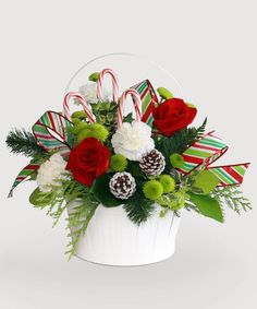 Festive white basket filled with traditional holiday colors and candy cane accents. Pumpkin Floral Arrangements, Christmas Flower Arrangements, Modern Flower Arrangements, Christmas Flowers, Christmas Mugs, All Things Christmas, Christmas Themes, Christmas Holidays, Christmas Wreaths