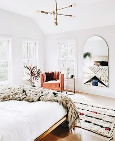 Bright white master bedroom with gorgeous wall mirror and leather chair. brass light fixture.