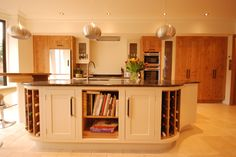 Large Greenheart Kitchens island unit with curved ends, wine racks, book case and seating