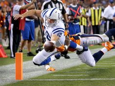 Indianapolis Colts Andrew Luck dives for a 2nd quarter touchdown as Denver Broncos Nate Irving attempts to stop him. The Indianapolis Colts play the Denver Broncos Sunday, September 7, 2014, evening at Sports Authority Field at Mile High in Denver CO.