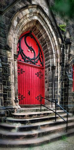Dramatic red door trimmed in black scroll-work rivets the eye with its soaring Gothic arch. Beautiful finishing touch on this majestic building!