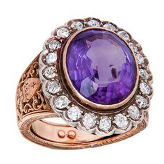 Circa: 1930s 18K yellow Gold Bishops Ring. Centrally set with an Oval Amethyst Approximately 12 to 14 Carats and surrounded by approximately 2 Carats of old Mine Cut Diamonds. The sides feature very fine hand engraved detail work.