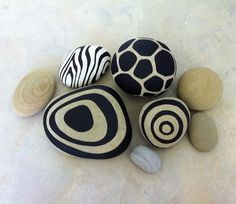 Painted rocks - abstract designs in black on pale rocks. DO