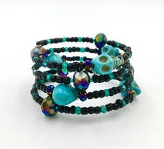 Black and teal memory wire wrap bracelet made with glass Czech beads, dark iris rainbow AB crystals, and turquoise skull beads. **Read my FAQs below and if you have any further questions or comments please do not hesitate to contact me!**