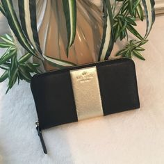 Authentic Kate Spade Wallet Cedar Street Racing Stripe Lacey. Black and Gold with a zipper middle. Credit card slots on two sides. Bill compartments on the inside and out. Lots of room for pics and has around zip closure. kate spade Bags Wallets