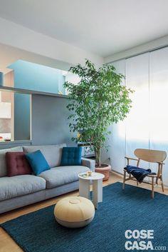 zona conversazione, dettagli, divano grigio, cuscini trapuntati, poltroncina di legno, pouf, tappeto color petrolio, tavolino bianco, tende a pannello, parete divisoria