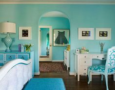 This bedroom has a very pretty blue theme to it. The trunck at the end of the bed is a darker blue compared to the walls and chair which are a light blue.