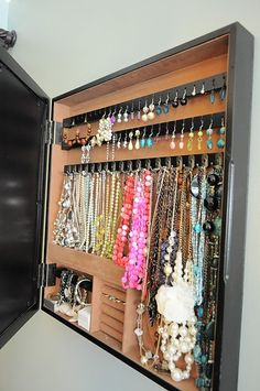 Organize jewelry behind a picture frame...brilliant.