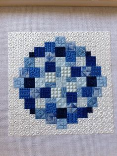 circular needlepoint in blue, stitch sampler