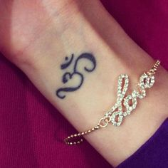 What does om tattoo mean? We have om tattoo ideas, designs, symbolism and we explain the meaning behind the tattoo. Unity Tattoo, Ohm Tattoo, Om Symbol Tattoo, Chakra Tattoo, Ohm Symbol, Wrist Tattoo, Om Tattoo Meaning, Tattoos With Meaning, Yoga Tattoos