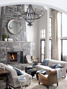Slipcovered Shabby Chic sofas, heaped with hand-sewn pillows, flank this living room's fireplace. The leathered armchair is by Jean de Merry. A custom-made antler table is a nice touch, playing up the lodge-like interior. The walls are Benjamin Moore's Collingwood, a grayish-white hue, providing a softer look that a bright white. Adding a few choice color choices, like the blue plaid throw pillows gives the space a strong sense of color and pattern.