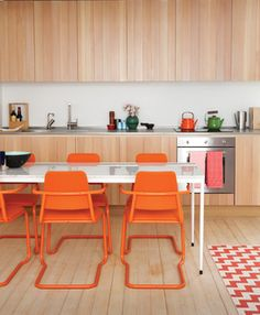 In this custom-built London guesthouse kitchen designed by Studiomama, lustrous vertically clad cabinetry achieves additional depth with the addition of the chairs, which were picked up for $15 each at a local market and powder coated in bright orange.