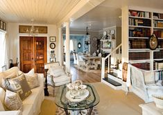 Seaside romance, love the bookshelf on the other side of the staircase and the 2 wood front doors.