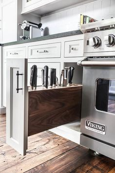 Well appointed kitchen boasts rustic wood floors and a stainless steel Viking oven placed beside a knife rack hidden in a white pull-out drawer adorning a polished nickel pull. Tidy Kitchen, Kitchen Rack, Kitchen Stove, Diy Kitchen Decor, Kitchen Drawers, Kitchen Knives, Kitchen Appliances, Home Decor, Kitchen Ideas