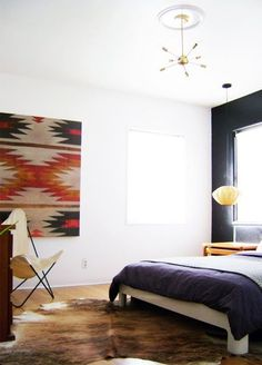 mid-century bedroom with charcoal wall + hide rug + woven textile art + sputnik