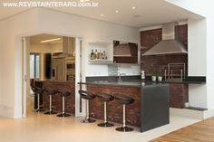 A cozinha e o espaço gourmet são separados apenas por uma porta de vidro que, quando aberta, integra totalmente os ambientes. A unidade visual é acentuada pela bancada em tijolos da Palimanan e tampo em granito.