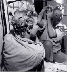She pin curled her hair for most of the 1950s although she began to wear her hair in a straighter style as the 1960s approached/up until her death. You can see her pin curling her hair here: