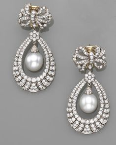 A pair of cultured pearl, diamond and eighteen karat white gold pendant earrings